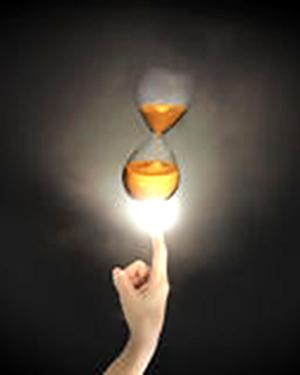 finger-humano-que-seala-en-el-reloj-de-arena-con-la-luz-brillante-58850316